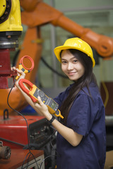 Manufacturing worker operating a robot machine