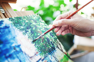 woman is painting some picture with paintbrush