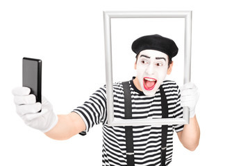 Mime artist taking selfie behind a picture frame