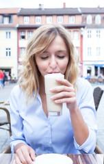 Frau mit blonden Locken geniesst einen Kaffee Latte
