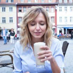Frau mit blonden Locken liebt Kaffee Latte