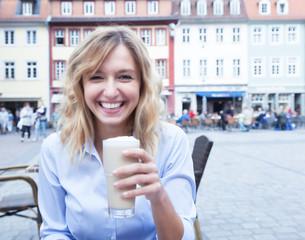 Lachende Frau mit blonden Locken trinkt Latte im Strassencafe