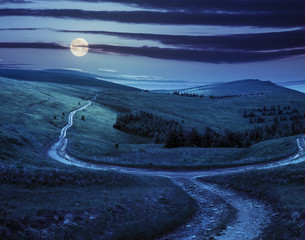 cross road on hillside meadow in mountain at sunrise at night