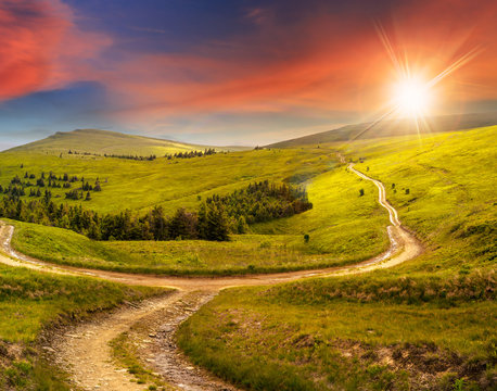 cross road on hillside meadow in mountain at sunrise at sunset