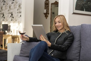 Young Woman Reading a Digital Tablet on Sofa