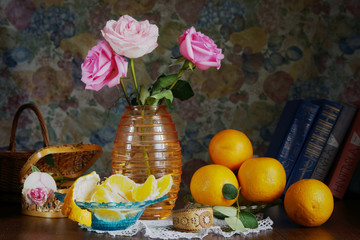 Rural still life with roses in a vase and oranges