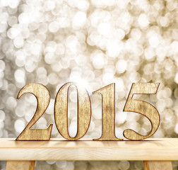 2015 year wood number on wooden table with sparkling bokeh