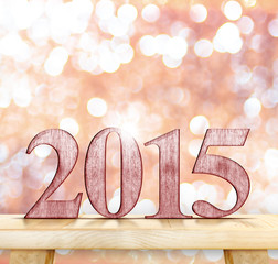 2015 year number on modern wooden table with sparkling bokeh