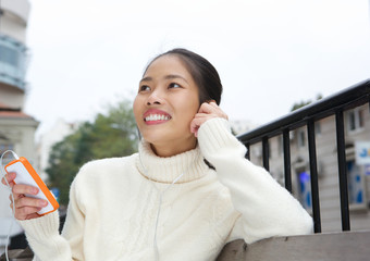 Smiling young woman listening to music on mobile phone
