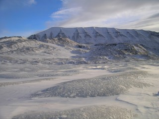 Glacier surface surrounded by mountains in high-Arctic