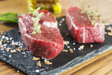 Raw beef tenderloin with spices over a blackboard
