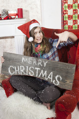 Beautiful girl in Santa Claus hat showing wooden signboard with