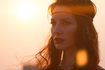 Portrait hippie woman with headband looking far away at sunset
