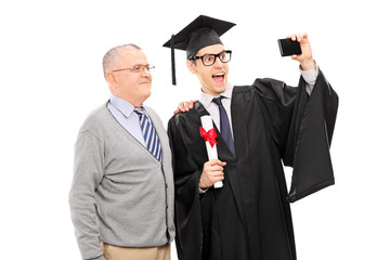 College graduate taking a selfie with his father