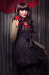 beautiful young woman posing with red lace umbrella against retr