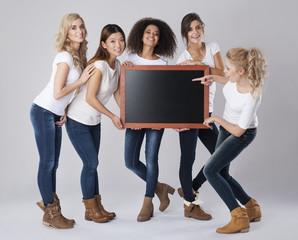 Beautiful girls holding empty blackboard