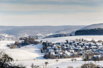 Winterlandschaft mit Ortschaft und Hügeln