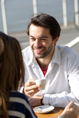 Happy young man drinking coffee with woman