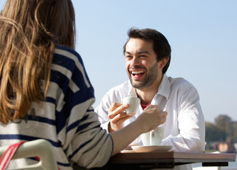 Happy man drinking coffee with woman at outdoor cafe