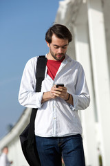 Young man with bag walking and sending text message outdoors