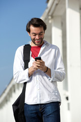 Young man smiling and looking at mobile phone