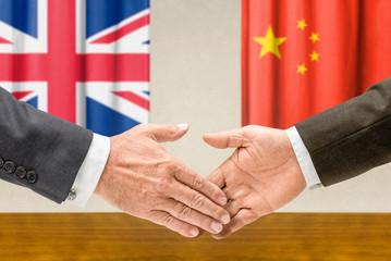 Vertreter Großbritanniens und Chinas reichen sich die Hand