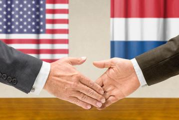 Vertreter der USA und der Niederlande reichen sich die Hand