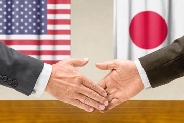 Vertreter der USA und Japans reichen sich die Hand