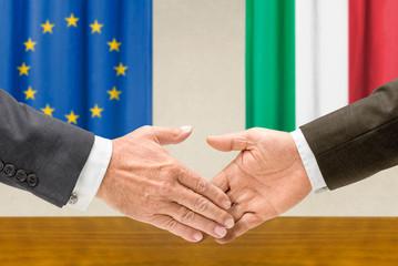 Vertreter der EU und Italiens reichen sich die Hand