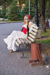 The girl in the image of Santa Muerte is sitting on a bench