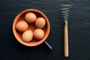 Top view of eggs in a bowl and an eggbeater