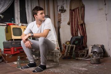 Sitting Man at Junk Room Looking at Right Frame