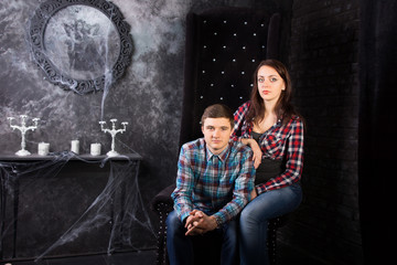 Young Couple Sitting in Creepy High Back Chair