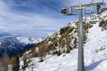 Mountain slopes and chairlift in winter on a sunny day