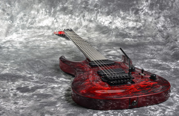 red seven-stringed electric guitar  on white-gray background