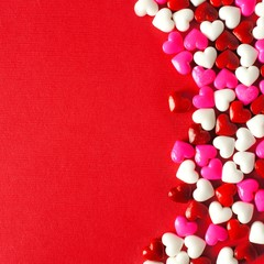Valentines Day candy curved border on a red paper background