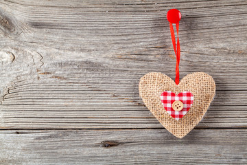 Heart shaped decoration made of wood, over wooden background