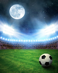 Soccer ball in grass, soccer stadium with the dright lights