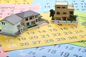 カレンダーの上に住宅模型を置いている様子