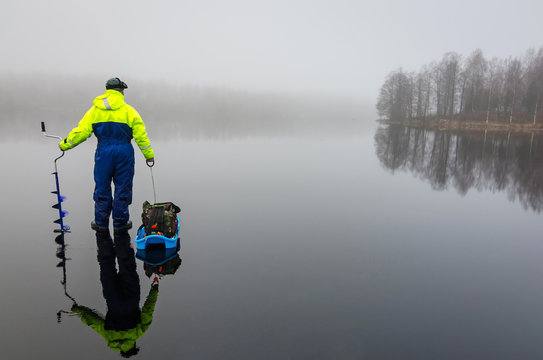 Angler with fishing equipment on the ice