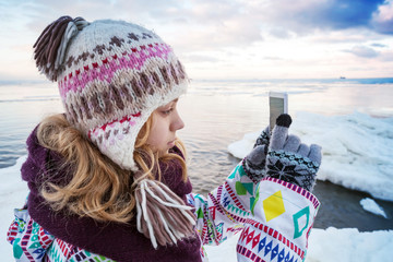 Little blond girl taking pictures on her smartphone