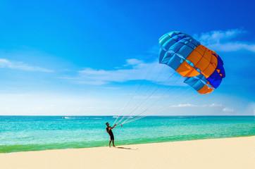 Thai man taking off with parasail on Phuket, Thailand