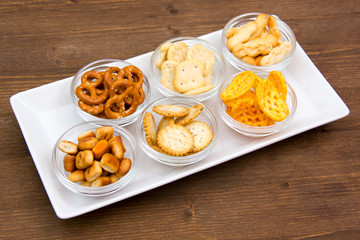 Bowls of pretzels on tray seen from above on wooden table