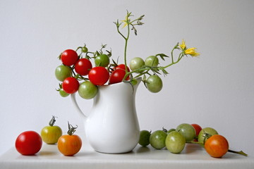 Kitchen still life with green and red tomatoes in a white jug