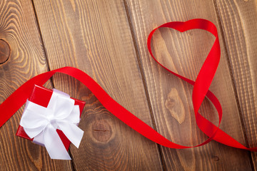 Heart shape ribbon and gift box over wood valentines day backgro