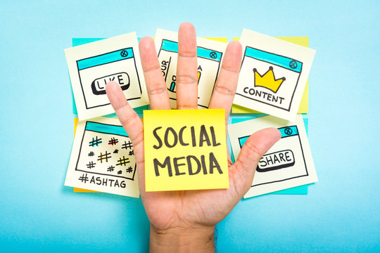 Sticky note with social media on hand with blue background.