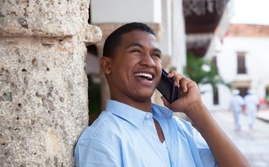 Fröhlicher junger Mann aus Südamerika mit Handy
