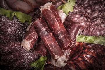 Slices of different kinds of meat with green salad. Toned
