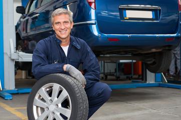 Tyre Dealer Holding A Tire