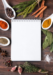 Fresh herbs, different spices notebook on the table